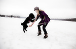 A Blonde Woman Posing and Having Fun with her Dog on Snowy Landscape