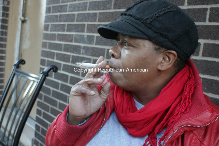 WATERBURY, CT: 16 Nov. 2015: 171115CB03: WATERBURY -- Jacquiline Riddick smokes a cigarette Monday at the Truman Apartments public housing units in Waterbury where she lives. The U.S. Department of Housing and Urban Development has proposed a ban on smoking inside public housing housing units as well as outdoors within 25 feet of housing buildings. Riddick opposes the proposed ban. Caleb Bedillion Republican-American