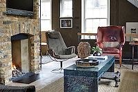 The living room is furnished with a mixture of retro and modern furniture grouped around a brick fireplace