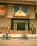 CHINA, Shanghai, two people riding bicycle, passing through building
