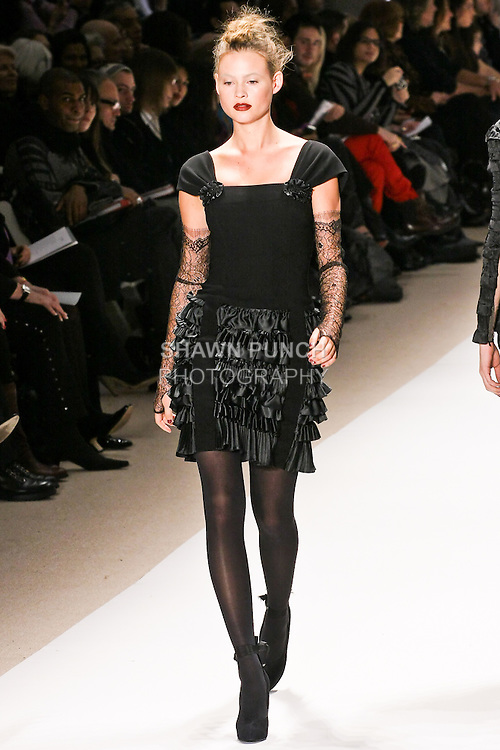 Behati Prinsloo walks the runway in a black crepe cocktail dress with laser cut ruffles, by Georges Chakra for the Edition Autumn Winter 2010-2011 collection, during Mercedes-Benz Fashion Week Fall 2010.