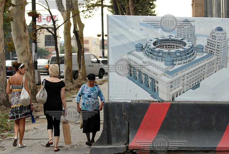 Pedestrians walk along one of the capital's main streets, Rustaveli Avenue, past a poster advertising a new international hotel under construction.