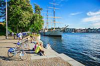 Människor sitter på en trappa på en kaj vid vattnet på Skeppsholmen Stockholm.