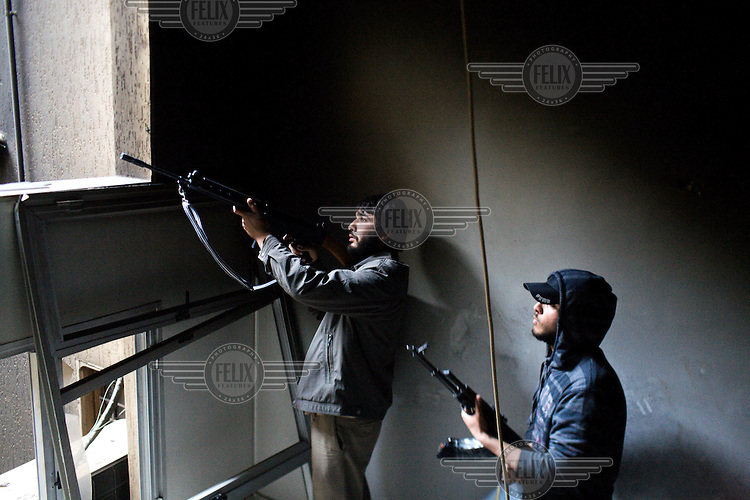 Rebel fighters stand at a window as they fire on Gaddafi forces in central Misurata. On 17 February 2011 Libya saw the beginnings of a revolution against the 41 year regime of Col Muammar Gaddafi.Hours later Guy Martin was seriously injured in an RPG attack.