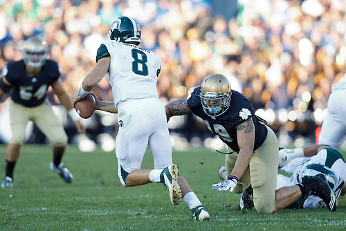 Michigan State quarterback Kirk Cousins (#8) escapes the rush of Notre Dame defensive end Aaron Lynch (#19) in action during NCAA football game between Notre Dame and Michigan State.  The Notre Dame Fighting Irish defeated the Michigan State Spartans 31-13 in game at Notre Dame Stadium in South Bend, Indiana.
