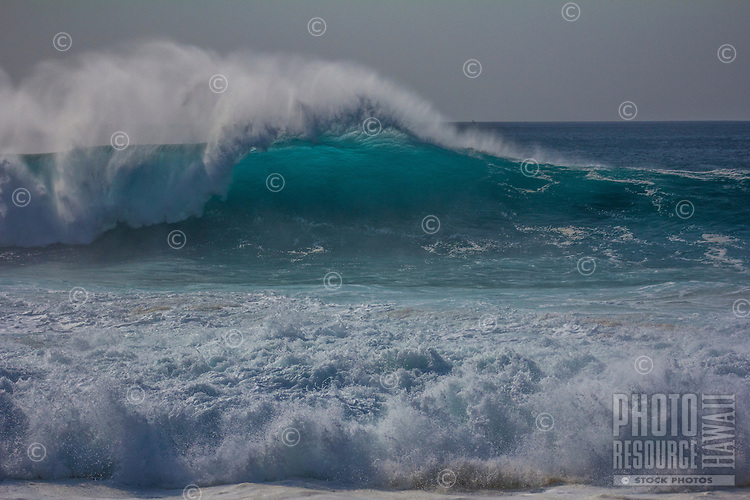 A large wave lights up from the afternoon sun and is carried by strong offshore winds at Ke Iki on the North Shore of O'ahu.