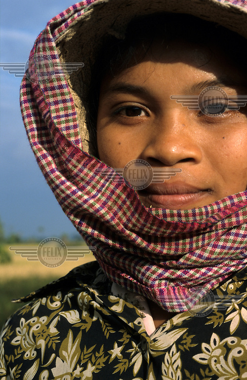 A portrait of a young woman working in the paddy fields during the harvest.
