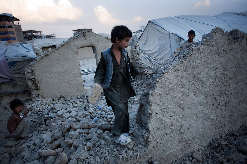 A displaced Afghan boy uses a brick to tear down the mud and brick wall of a destroyed house in Chamane Babrak, a tented slum community for displaced Afghans just west of Kabul, Afghanistan, Monday, Oct 5, 2009. The majority of the familes in Chamane Babrak are returnees from Iran.