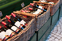 Bottles of wine are displayed in wicker baskets outside a liquor shop in Paris.