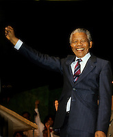 Montreal (Qc) CANADA, June 20, 1990 File Photo.<br /> <br /> South African opposition leader Nelson Mandela (R) raise his fist to salute the crowd right after his speech in front the black community in Montreal (Quebec, Canada) on June 20, 1990, while Jean Dore (L) ; the Mayor of Montreal at that time is applauding.<br /> <br /> Photo (c) 1990, by Pierre Roussel - IMAGES DISTRIBUTION