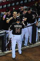 May 13, 2012; Phoenix, AZ, USA; Arizona Diamondbacks second baseman Ryan Roberts (14) is congratulated by manager Kirk Gibson (right) and catcher Miguel Montero after scoring in the second inning against the San Francisco Giants at Chase Field. Mandatory Credit: Mark J. Rebilas-