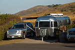 GMC Yukon SUV and Airstream travel trailer in camp on the California Coast
