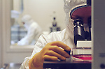 Technician evaluating specimen with microscope in genetics research laboratory clean room