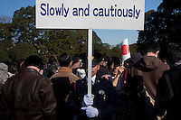 A Policeman warns well wishers to exit the Imperial Place slowly and cautiously after the Emperor`s appearance. Emperor Akihito 76th birthday was celebrated in Japan with a national holiday and thousands of well-wishers being allowed into the Royal Palace for the occasion. He made three such appearances during the day and spoke of the economy difficulties many Japanese people are suffering during his address. He was accompanied by Empress Michiko, Crown Prince Naruhito, Prince Akishino and their wives. Tokyo, Japan December 23rd 2009