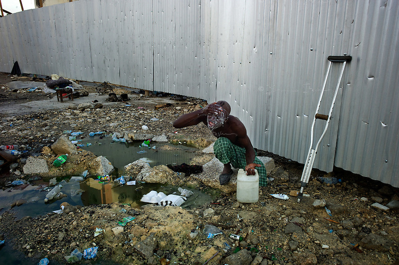 Port Au Prince, Haiti, April 10, 2010.A handicapped man washes in the street where he slept, right by the destroyed Cathedral..