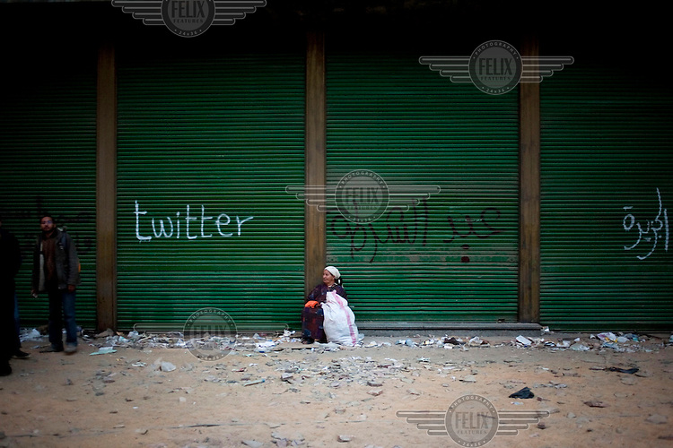 A woman rests in front of a closed shop front in Tahrir Square. A graffiti on the shutter reads 'Twitter'. Throughout Friday, 4 February, anti government protesters protected their positions from pro Mubarak supporters around Tahrir square, the scene of heavy clashes between pro and anti government protesters. Continued anti-government protests take place in Cairo calling for President Mubarak to stand down. After dissolving the government and allowing for talks with opposition parties Mubarak still refuses to step down from power...