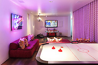A retro themed entertainment room with a fooseball table and air hocky