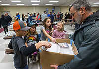 NWA Democrat-Gazette/BEN GOFF @NWABENGOFF<br /> Bear Ortega (from left), 9, sister Vivianne Ortega, 7, sister Leighton Ortega, 10, and friend Bowen Powell, 5, top off boxes with cranberry sauce as Brian Jackson collects a box for delivery Thursday, Nov. 28, 2019, during the annual Thanksgiving meal distribution at the First Baptist Church Olive Street campus in Rogers. <br /> <br /> Paul Olinger, a church member who helped coordinate the meal, said the event started 20 years ago 'As an outreach of the church to show the love of Christ in the community'. Volunteers from the church and the community cooked, packaged and delivered boxed meals that included ham, green beans, mashed potatoes and deserts. <br /> <br /> Open to anyone, a line wrapped around the room as families picked up boxes of food to take home, but Olinger estimates that 98 percent of the meals are delivered by volunteers.
