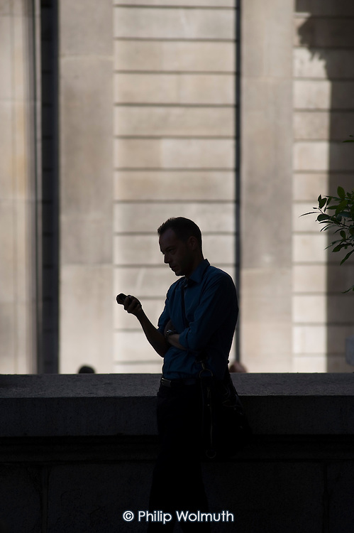 Man using a mobile phone outside the Bank of England, Threadneedle Street, City of London.