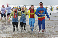 Pictured: Four people in Mininon and super hero costumes take to the sea. Tuesday 26 December 2017<br /> Re: Hundreds took part in this year's Boxing Day Walrus Dip which see people in fancy dress taking to the sea at Cefn Sidan beach in Pembrey Country Park, west Wales, UK.