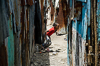 A Haitian girl runs in a corridor between shacks in the slum of Cité Soleil, Port-au-Prince, Haiti, 24 July 2008. Cité Soleil is considered one of the worst slums in the Americas, most of its 300.000 residents live in extreme poverty. Children and single mothers predominate in the population. Social and living conditions in the slum are a human tragedy. There is no running water, no sewers and no electricity. Public services virtually do not exist - there are no stores, no hospitals or schools, no urban infrastructure. In spite of this fact, a rent must be payed even in all shacks made from rusty metal sheets. Infectious diseases are widely spread as garbage disposal does not exist in Cité Soleil. Violence is common, armed gangs operate throughout the slum.