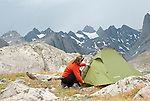 A young woman sets up her tent while camping in Titcomb Basin, Wind River Mountains,  Wyoming.