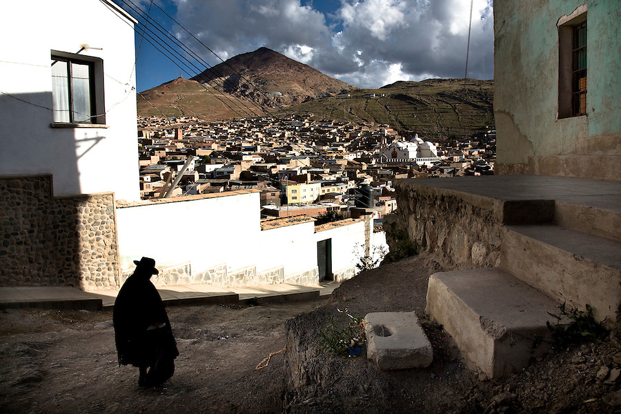 A quechuan woman descending an alleyway in the city of Potosí.