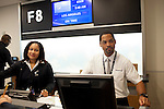 Delta employees, including AJ Clemons (left), prepare to check-in passengers before a flight to Los Angeles at gate F8 in the international terminal.