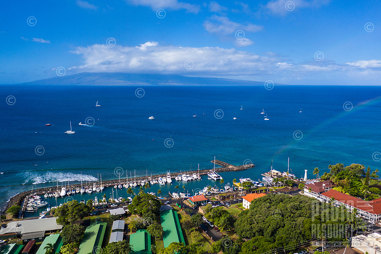 An aerial view of Maui's Lahaina Harbor with a rainbow on the right, with Lana'i in the distance.
