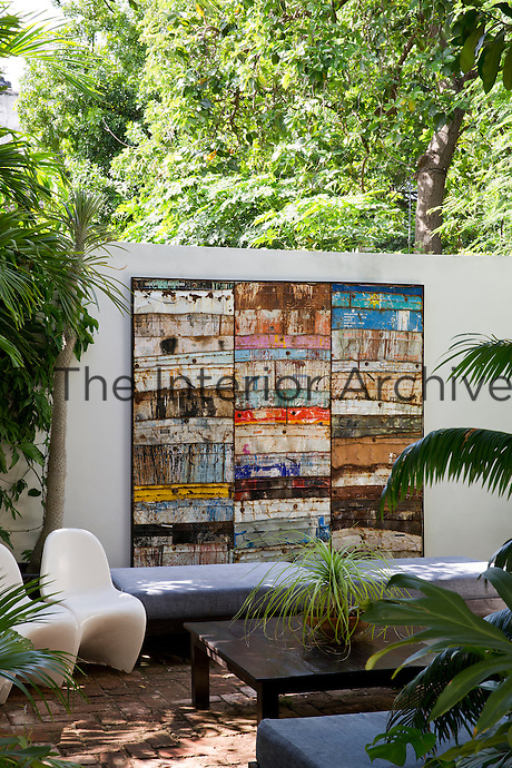 An artwork by Damian Aquiles adorns a concrete wall enclosing this outdoor sitting area