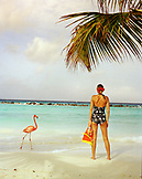 ARUBA, portrait of young woman standing on the beach in the middle of Pink Flamingos, Renaissance Island