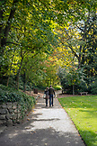 USA, Oregon, Ashland, a young man and woman walk through Lithia Park in the Fall