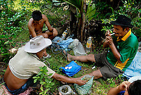 Rene Arandia Vargas, right, along with Francisco Bonefar, left front, and Francisco's son, smoke cigarettes and chew on coca leaves after a hour and half hike into the Chaparé jungle to find Varas's coca farm near Eterezama, Bolivia. VThe group will work for almost eight hours, and say that the that the work would be impossible without the help and energy they recieve from chewing the coca leaf.
