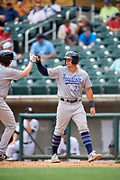 Pensacola Blue Wahoos left fielder Brian O'Grady (21) high fives Gavin LaValley (25) after he hit a home run in the top of the seventh inning during a game against the Birmingham Barons on May 9, 2018 at Regions Field in Birmingham, Alabama.  Birmingham defeated Pensacola 16-3.  (Mike Janes/Four Seam Images)