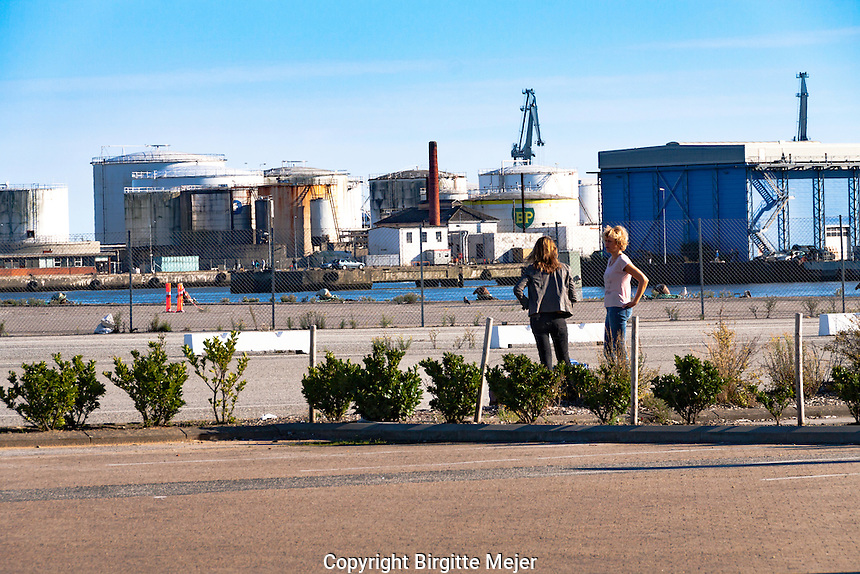 2 women talking on the pier in a Scandinavian harbour, with the sky and silo's as backdrop<br /> <br /> Editorial use only.