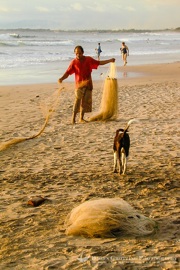 Bali, Badung, Kuta. A fisherman prepares his net on Kuta Beach.