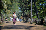A woman walks down a road in the Cambodian village of Somrith.