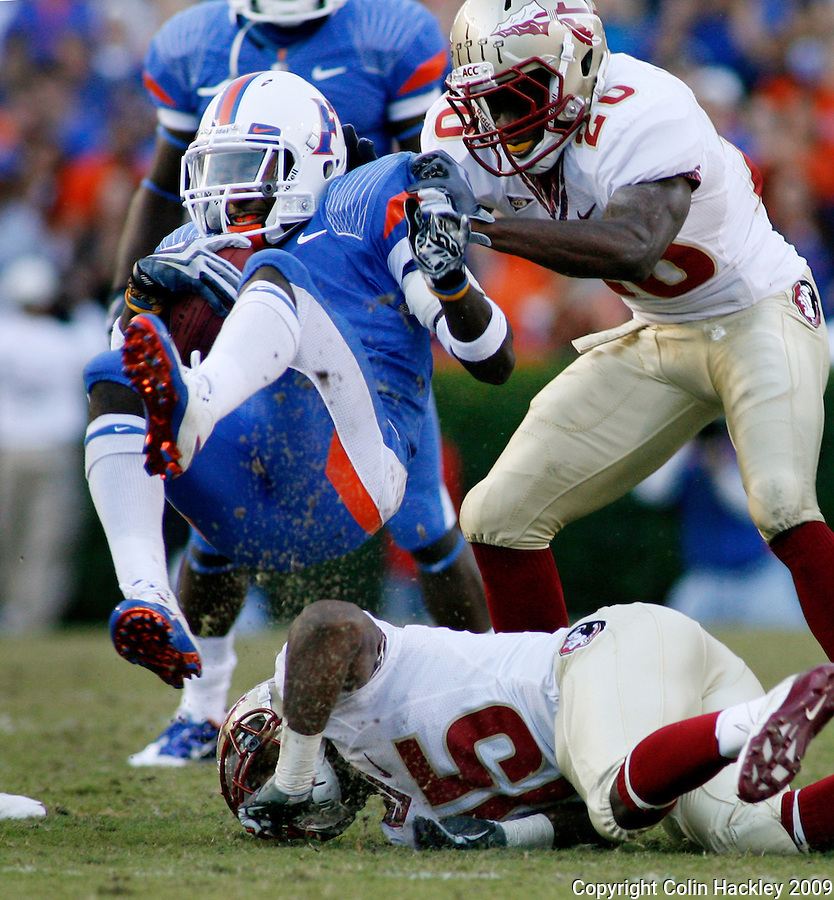 GAINESVILLE, FL 11/28/09-FSU-UF FB09 CH11-Florida's Chris Rainey is up ended by Florida State's Ochucko Jenije, belowm and Jamie Robinson during first half action Saturday at Florida Field in Gainesville. .COLIN HACKLEY PHOTO