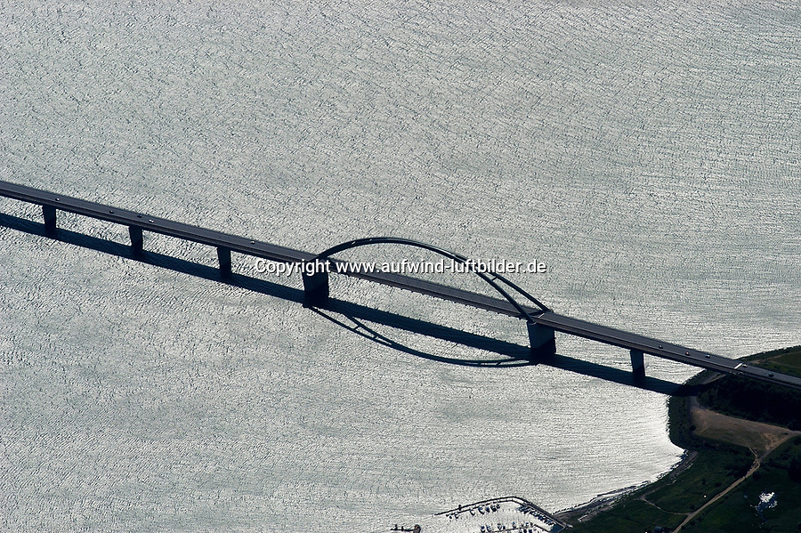 4415/Fehmarnsundbruecke :EUROPA, DEUTSCHLAND, SCHLESWIG- HOLSTEIN, 07.06.2005: Die Fehmarnsundbruecke verbindet die Insel Fehmarn in der Ostsee mit dem Festland bei Großenbrode.<br />Die 963 Meter lange kombinierte Straßen- und Eisenbahnbruecke ueberquert den 1.300 Meter breiten Fehmarnsund, hat eine lichte Hoehe von 23 Metern ueber dem Mittelwasser und wurde 1963 in Betrieb genommen. Zeitgleich wurde die Faehrlinie von Großenbrode-Kai nach Gedser durch die Faehrlinie Puttgarden-Rødby (Daenemark) ersetzt. Durch die Fehmarnsundbruecke und den gleichzeitig gebauten Faehrhafen Puttgarden auf Fehmarn wurde die durchschnittliche Reisezeit auf der so genannten Vogelfluglinie von Hamburg nach Kopenhagen deutlich verkuerzt. Ostsee, Meerenge, Vogelfluglinie, Bundesstrasse B207, Europastrasse E47, Verbindung nach Skandinavien, Insel, Wasser, Meer, Luftaufnahme, Luftbild,  Luftansicht
