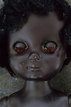 Close up of head and shoulders of modern plastic black girl doll slightly scratched and soiled lying on rusty metal sheet
