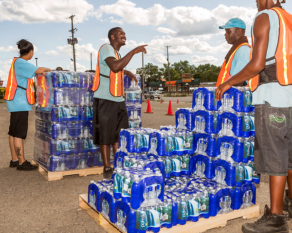 August 6, 2016. Flint, Michigan. <br />  Zanando Jacobs, center, talks with his fellow employees at a bottled water distribution point. <br />  Although Flint city government says their water is safe to drink when filtered properly, many residents still rely on bottled water for drinking and bathing. Through federal emergency funds, the state distributes 1000's of cases of bottled water nearly every day to Flint residents.<br />  In April 2014, the city of Flint switched its water source from the Detroit Water and Sewerage Department to using the Flint River in an effort to save money. When the switch occurred, the city failed to have corrosion control treatment in place for the new water. This brought about a leaching of lead from pipes into the water, increasing the lead content in the drinking water to levels far above legal limits. After independent sources brought this to light, the city admitted the water was unsafe and legal battles have ensued between resident and the local and state governments.