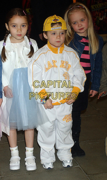 BROOKLYN BECKHAM & COUSIN LIBERTY (left).Scooby Doo 2 premiere at Warner Village, Islington.26 March 2004.full length, full-length, los angeles lakers white tracksuit, yellow baseball cap, hat .www.capitalpictures.com.sales@capitalpictures.com.©Capital Pictures