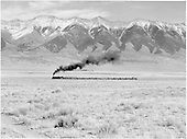 Distant full-length view of D&amp;RGW #480 with northbound freight train against backdrop of Sangre de Cristo Mountains.<br /> D&amp;RGW  near Villa Grove, CO  Taken by Richardson, Robert W. - 11/1950