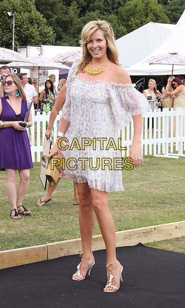 PENNY LANCASTER STEWART .Duke Of Essex Polo Trophy at Gaynes Park, Epping, Essex, England, UK,.July 4th 2009..full length white sheer puff sleeve off the shoulder dress blouson strappy sandals gold straw clutch bag print.CAP/ROS.©Steve Ross/Capital Pictures