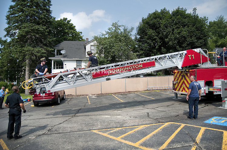 TORRINGTON, CT, 06  JULY 15 - Torrington firefighters lower a medical patient to the ground after using the ladder truck to remove her from the second floor of 472 East Main St. Monday afternoon. Medics responding to a call with firefighters discovered a partially collapsed stairwell leading to the second floor.  Alec Johnson/ Republican-American