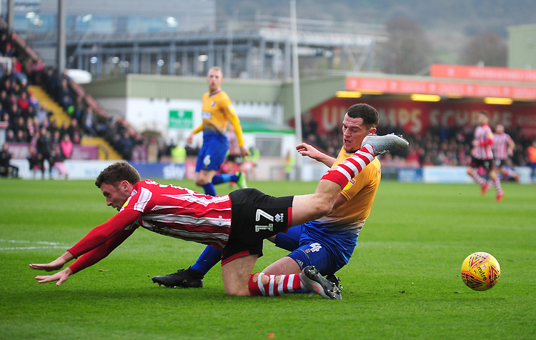 Lincoln City's Shay McCartan is tackled by Mansfield Town's Matt Preston<br /> <br /> Photographer Andrew Vaughan/CameraSport<br /> <br /> The EFL Sky Bet League Two - Lincoln City v Mansfield Town - Saturday 24th November 2018 - Sincil Bank - Lincoln<br /> <br /> World Copyright © 2018 CameraSport. All rights reserved. 43 Linden Ave. Countesthorpe. Leicester. England. LE8 5PG - Tel: +44 (0) 116 277 4147 - admin@camerasport.com - www.camerasport.com