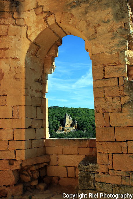 The 15th Century French Château de Laussel revealed through an arched window of the 12th Century medieval fortress Commarque in the picturesque Dordogne region of France.