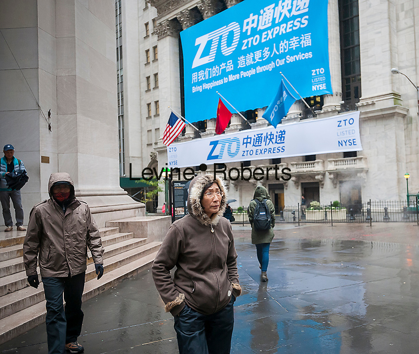 Asian tourists in front of the New York Stock Exchange decorated for the first day of trading for the ZTO Express IPO on Thursday, October 27, 2016. The initial public offering of the Chinese package delivery service is the largest IPO by a Chinese company since the Alibaba IPO in 2014. 72.1 million shares were priced at $19.50 per share. 75 percent of ZTO Express' business comes from Alibaba. (© Richard B. Levine)