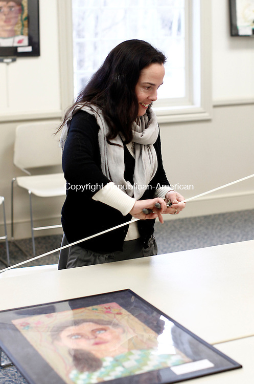 Southbury, CT- 02 March 2014-030214CM01-  Southbury art educator, Margaret Murphy sets up artwork at the Southbury Public Library on Monday. Pinto was working with other educators setting up pieces of artwork showcasing artwork from students from Gainfield and Pomperaug Elementary Schools as well as Rochambeau Middle School. The artwork will hang in the library, and is part of Youth Art Month which will run through March. The gallery is a step-in to the Region 15 Art Gallery Show, which will run April 25 from 6 p.m. to 9p.m. and April 26th 10 a.m. to 2 p.m. at Pomperaug High School and will feature artwork from students from Region 15 grades K through 12.     Christopher Massa Republican-American