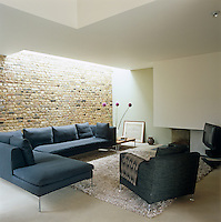 An L-shaped Italian sofa defines the living room with a basalt hearth and exposed brick wall